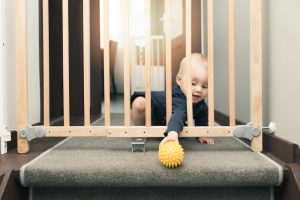 Child,Playing,Behind,Safety,Gates,In,Front,Of,Stairs,At